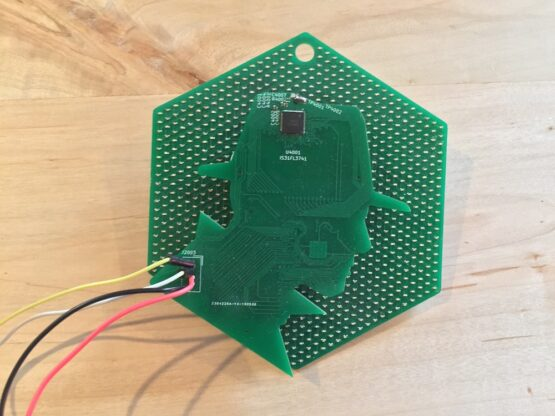 Hexagon board with LED under a silhouette-shaped controller board